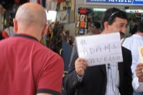 Водитель такси, держа в руках табличку с именем клиента ожидает его в начальной точке путешествия